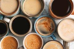Muitos copos do café quente aromático diferente na opinião de tampo da mesa Imagens de Stock