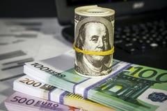 Muitos dólares e euro na tabela Imagens de Stock Royalty Free