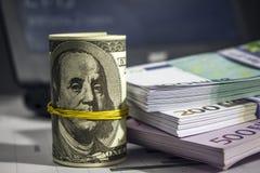 Muitos dólares e euro na tabela Foto de Stock