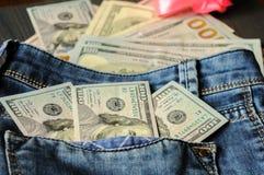 Muitos dólares em um bolso das calças de brim O dinheiro está em toda parte foto de stock