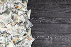 Muitos dólares em um fundo de madeira imagens de stock royalty free