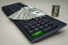Muitos dólares em um teclado de computador Fotos de Stock Royalty Free