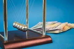 muitos d?lares do dinheiro e bolas do newton em um fundo azul fotografia de stock