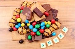 Muitos doces com açúcar da palavra na superfície de madeira, alimento insalubre Foto de Stock Royalty Free