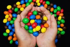 Muitos doces nas mãos do ` s das crianças, vista superior da cor imagem de stock