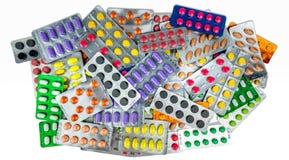 Muitos dos comprimidos da tabuleta isolados no fundo branco Comprimidos amarelos, roxos, pretos, alaranjados, cor-de-rosa, verdes Imagem de Stock