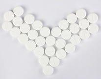 Muitos de comprimidos redondos no formulário do coração Foto de Stock