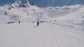 Muitos esquiadores que esquiam abaixo da montanha no inverno no resort de montanha filme
