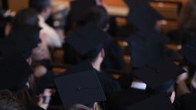 Muitos graduados da universidade que escutam o discurso e que aplaudem, concessão do diploma video estoque