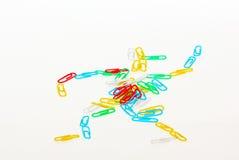 Muitos grampos coloridos estão na forma de um homem pequeno imagem de stock