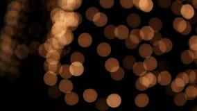 Muitos incandescem círculos brilhantes de Bokeh na noite filme