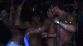 Muitos indivíduos alegres sem camisas que dançam no filme