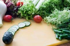 Muitos ingredientes para cozinhar a salada esverdeiam, vegetais em uma placa amarela imagens de stock royalty free
