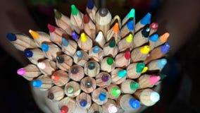 Muitos lápis coloridos nas mãos/lápis coloridos de madeira/ Fotos de Stock Royalty Free