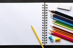 Muitos lápis coloridos no caderno branco para pintar Imagem de Stock