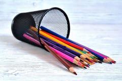 Muitos lápis multi-coloridos em um vidro da malha imagem de stock