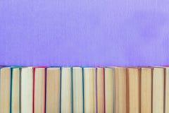 Muitos livros diferentes na parede violeta Fotografia de Stock