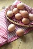 Muitos ovos crus marrons estão em uma cesta de vime na tabela Foto de Stock