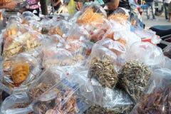 Muitos peixes secados e calamar secado em um saco de muitos pacotes Marisco que processa para a venda no mercado do local do mari fotos de stock