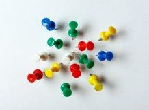 Muitos percevejos coloridos colaram em uma folha branca Foto de Stock Royalty Free