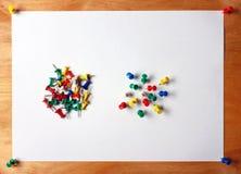 Muitos percevejos coloridos colaram em uma folha de papel branca unido à placa de madeira Imagem de Stock