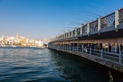 Muitos pescadores que ficam com os Ros na ponte na cidade de Istambul Foto de Stock