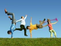 Muitos povos de salto na grama, colagem fotos de stock