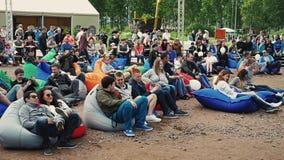 Muitos povos encontram-se em beanbags enormes na areia Festival do verão Dia ensolarado audiências video estoque