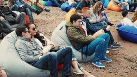 Muitos povos encontram-se em beanbags grandes na areia Festival do verão Dia ensolarado audiências filme