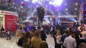Muitos povos no partido incorporado novo do ` s do ano com a árvore de Natal que pendura no teto no movimento rápido video estoque