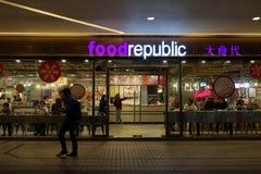 Muitos povos que comem algum alimento no centro da república do alimento na noite Foto de Stock