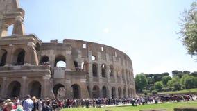 Muitos povos que veem Colosseum, atração turística famosa, Itália ensolarado, panorama filme