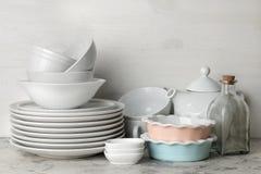 Muitos pratos diferentes dinnerware em um fundo do betão leve pratos para servir a tabela vários placas, bacias, e cu foto de stock royalty free
