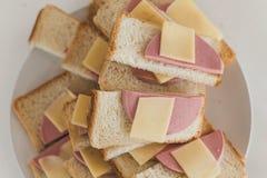 Muitos sanduíches com salsicha e queijo em uma placa Salsicha do doutor em partes de pão Petisco rápido para a empresa foto de stock