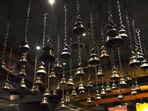Muitos sinos rituais que penduram em correntes do teto fotos de stock