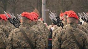 Muitos soldados em boinas vermelhas e suporte uniforme verde com suas partes traseiras à câmera filme