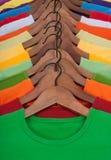 Muitos t-shirt vibrantes em ganchos de madeira Imagem de Stock Royalty Free