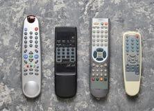 Muitos telecontroles da tevê em uma tabela concreta cinzenta Vista superior Controlo a distância dos aparelhos eletrodomésticos e Foto de Stock