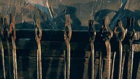 Muitos tenazes de brasa smithing colocados em uma cremalheira em uma forja video estoque