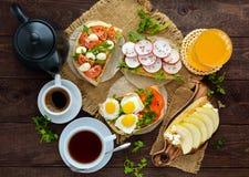 Muitos tipos dos sanduíches, do bruschetta, e do chá, café, suco fresco - para um café da manhã da família foto de stock