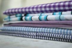 Muitos tipos dos tecidos de algodão nas listras e da gaiola em um fundo lilás foto de stock
