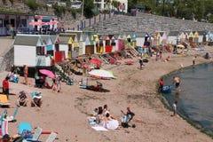 Muitos turistas na praia e cabanas da praia em cores diferentes na cidade Torquay Imagem de Stock