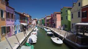 Muitos turistas que veem casas brilhantemente coloridas na rua da ilha de Burano, Veneza video estoque