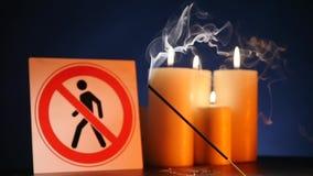Muitos velas claras de queimadura da cera com ondulação da chama amarela com o ` do sinal para a entrada dos povos são ` proibido filme