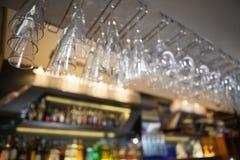 Muitos vidros de vinho que penduram acima da barra Fotos de Stock Royalty Free