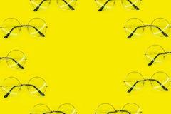 Muitos vidros redondos que encontram-se como o quadro no fundo amarelo Ponto de vista superior, configura??o lisa imagem de stock royalty free