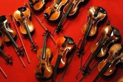 Muitos violinos e curvas no fundo vermelho foto de stock