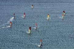Muitos windsurfers nas ondas efervescentes Fotografia de Stock