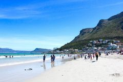 Muizenberg Beach. A bunch of beach going people and surfers  on a sunny day with mountain background at Muizenberg Beach, Cape Town, South Africa Stock Images