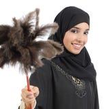 Mujer árabe del ama de casa que sonríe y que sostiene un plumero limpio Imagen de archivo